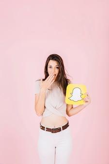 Überraschte frau, die snapchat ikone auf rosa hintergrund hält