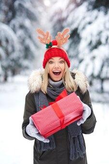 Überraschte frau, die weihnachtsgeschenk hält