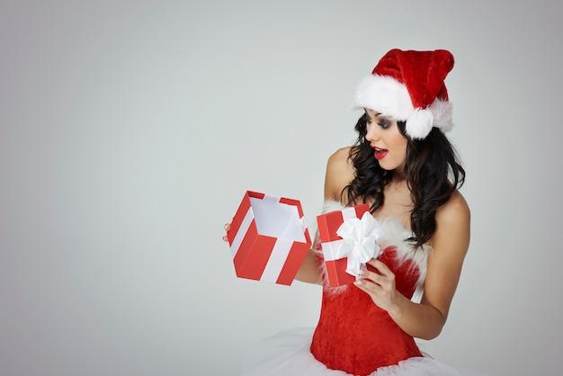 Überraschte frau, die weihnachtsgeschenk öffnet