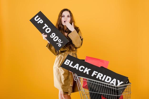 Überraschte frau im mantel mit schwarzem freitag 90% zeichen und bunten einkaufstaschen im warenkorb lokalisiert über gelb