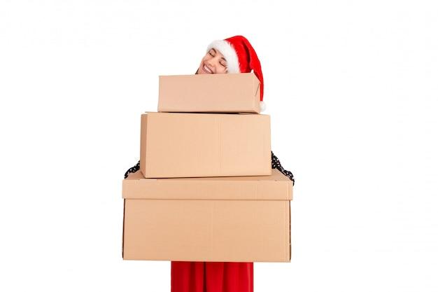 Überraschte frau im weihnachtshut, der weihnachtsgeschenk vor dem gesicht, lokalisiert auf weiß hält,
