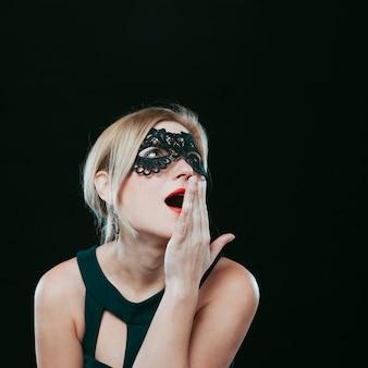 Überraschte frau in der dunklen karnevalsmaske