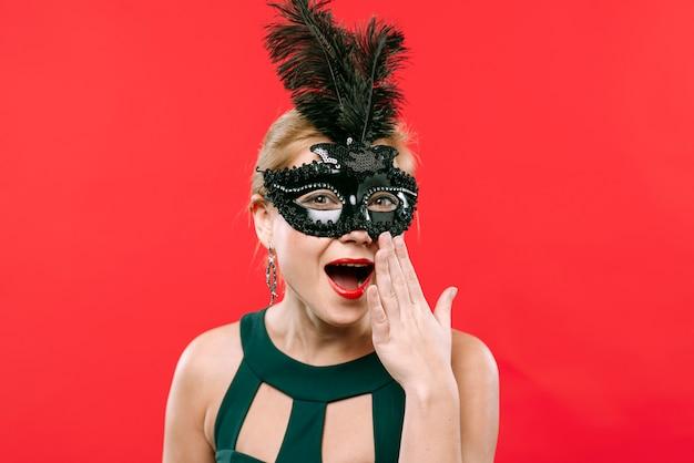 Überraschte frau in der schwarzen karnevalsmaske