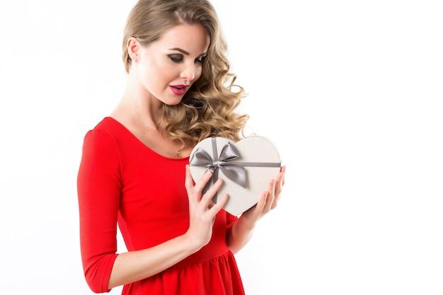 Überraschte frau in einem roten kleid mit einer geschenkbox in form eines herzens. isoliert. Premium Fotos