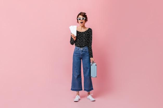 Überraschte frau in jeans, die karten an rosa wand halten