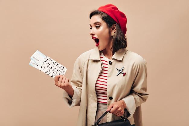 Überraschte frau in roter baskenmütze und beiger jacke schaut sich tickets an. stilvolle dame mit hellen lippen in baskenmütze, in beigem umhang und in gestreiften pulloverposen.