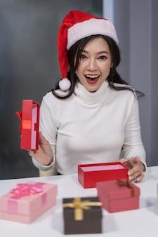 Überraschte frau in sankt hatte öffnende weihnachtsgeschenkbox