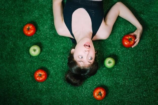 Überraschte frau inmitten von äpfeln und tomaten