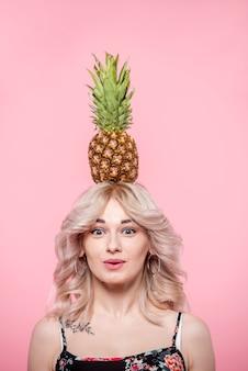 Überraschte frau mit ananas auf kopf