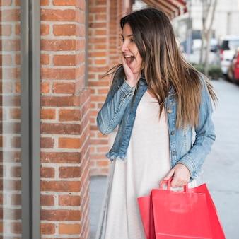 Überraschte frau mit den einkaufspaketen, die schaufenster betrachten