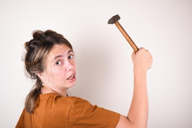 Überraschte frau mit einem hammer in den händen, die nicht weiß, wie man reparaturen im haus durchführt. frau mit einem hammer ist von der frage überrascht. das konzept der wahl der baustoffe