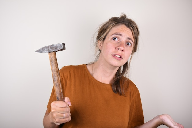 Überraschte frau mit einem hammer in den händen, die nicht weiß, wie man reparaturen im haus durchführt. frau mit einem hammer ist von der frage überrascht.