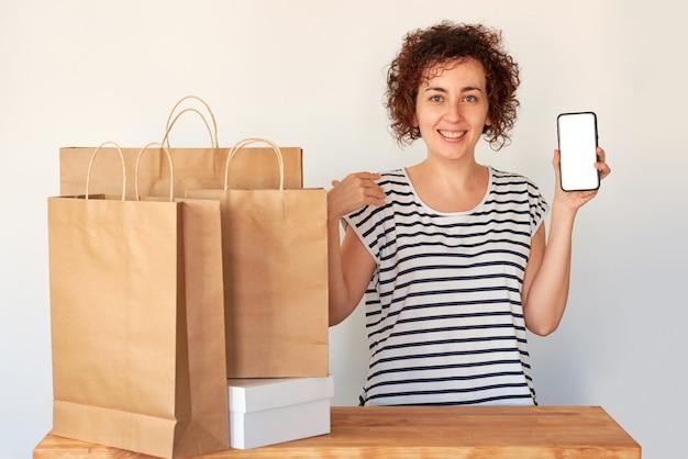 Überraschte frau mit einem smartphone neben einkaufstüten