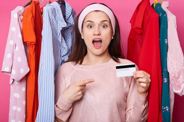 Überraschte frau mit geöffnetem mund hält kreditkarte. dame trägt rosa pulloverpunkte beiseite auf karte. ich bin froh, dass frau geld zum einkaufen hat. junges mädchen wählt kleidung im einkaufszentrum. mode, einkaufskonzept.