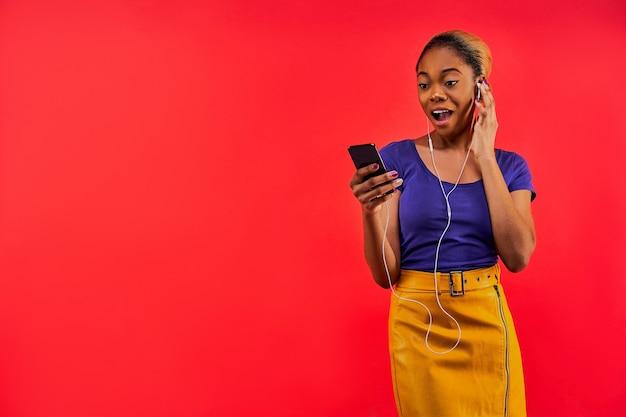 Überraschte frau mit in einem brötchen versammelten haaren hört musik in kabelgebundenen kopfhörern vom telefon