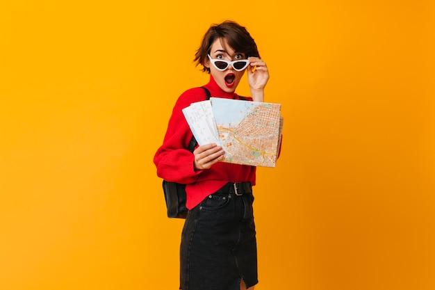 Überraschte frau mit karte, die sonnenbrille berührt