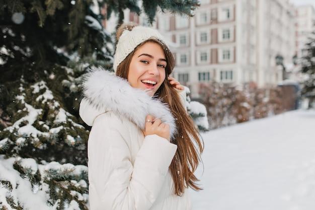 Überraschte frau mit langen glatten haaren, die spaß in den winterferien haben und zeit im freien verbringen. porträt der begeisterten kaukasischen frau im weißen outfit, das im park am verschneiten tag kühlt.