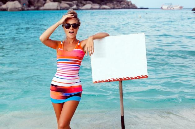 Überraschte frau mit leeren zeichen auf dem strand