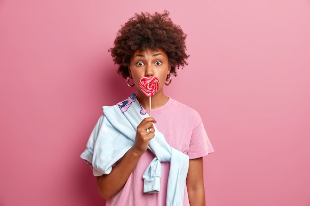 Überraschte frau mit lockigen haaren bedeckt den mund mit einem leckeren herzförmigen süßigkeitenlutscher, der mit ihrem freund im freien spazieren gehen wird, gekleidet in ein lässiges t-shirt und einen pullover, der über die schulter gebunden ist. menschen, jugendliche