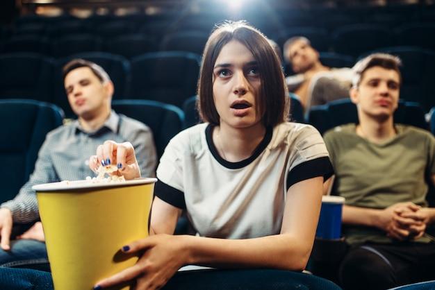 Überraschte frau mit popcorn, die film im kino sieht. showtime, film