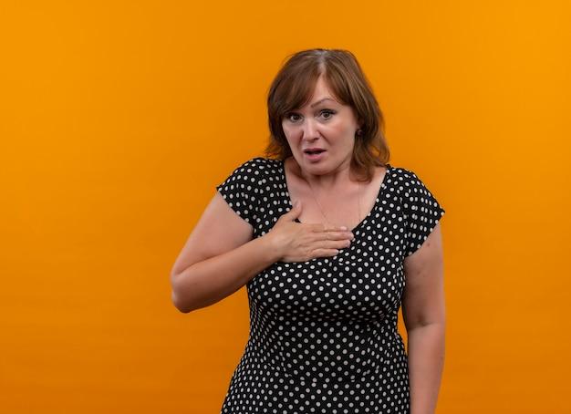 Überraschte frau mittleren alters, die hand auf brust auf isolierte orange wand mit kopienraum setzt