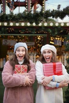 Überraschte frauen mit weihnachtsgeschenken auf weihnachtsmarkt