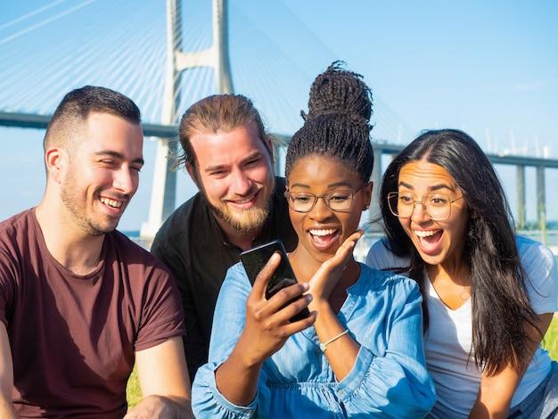 Überraschte freunde, die den smartphone im freien verwenden