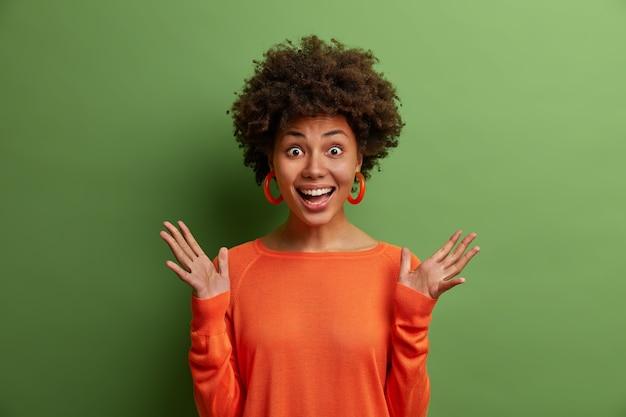 Überraschte fröhliche frau mit lockigem haar hebt die hände und fühlt sich beeindruckt, reagiert auf tolle überraschung von freund vorbereitet, trägt orangefarbenen pullover, isoliert auf grüner wand.