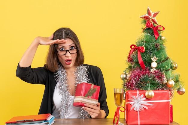 Überraschte geschäftsdame im anzug mit brille, die ihr geschenk hält und an einem tisch mit einem weihnachtsbaum darauf im büro sitzt