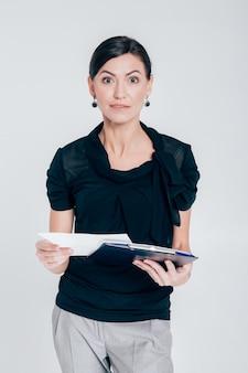 Überraschte geschäftsfrau, die einen ordner mit dokumenten auf einem grauen hintergrund hält