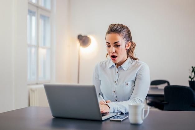 Überraschte geschäftsfrau, die laptopschirm betrachtet.