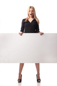 Überraschte geschäftsfrau, die plakat hält. isoliert auf weiß