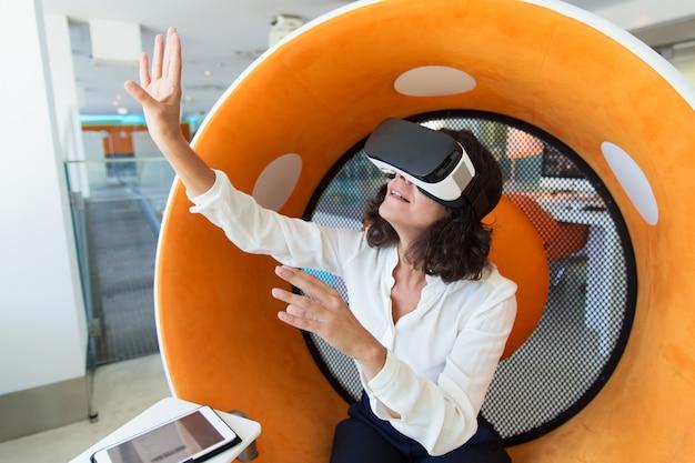 Überraschte geschäftsfrau, die virtuelle darstellung aufpasst