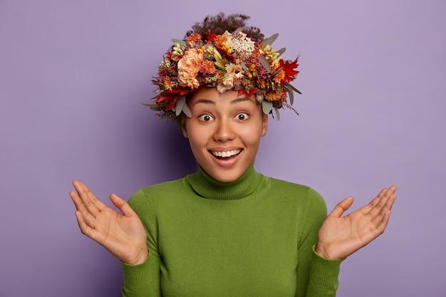 Überraschte glückliche ahnungslose frau breitet palmen aus, lächelt freudig, zeigt weiße zähne, trägt handgemachten herbstkranz und grünen rollkragenpullover, isoliert über lila hintergrund