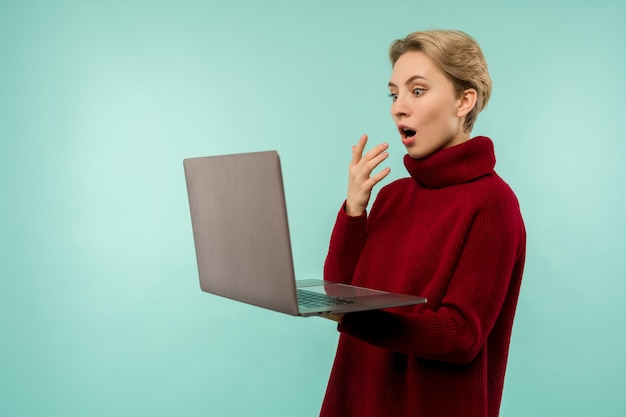 Überraschte glückliche blonde frau im pullover, der laptop-computerbildschirm mit offenem mund über blauem hintergrund sucht