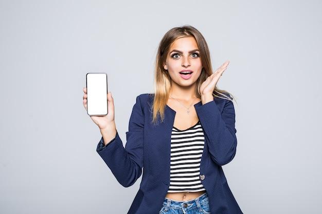 Überraschte glückliche brünette frau, die leeren smartphonebildschirm zeigt, während mit offenem mund über weiße wand schaut