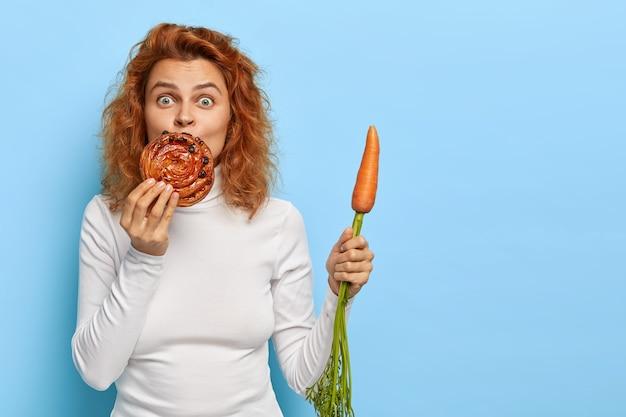 Überraschte gut aussehende fuchsfrau hält köstliche brötchen in der nähe des mundes, riecht angenehm nach geruch