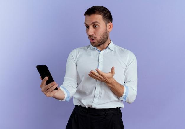 Überraschte gutaussehende mann hält hand offen halten und betrachten telefon isoliert auf lila wand