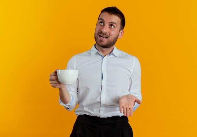 Überraschte gutaussehende mann hält tasse und schaut isoliert auf orange wand