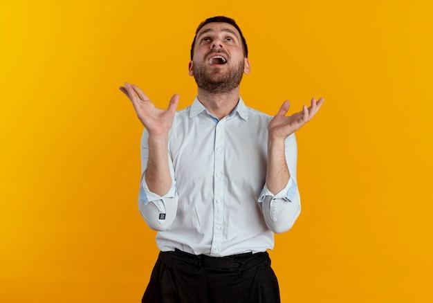 Überraschte gutaussehende mann schaut mit erhobenen händen auf orange wand auf