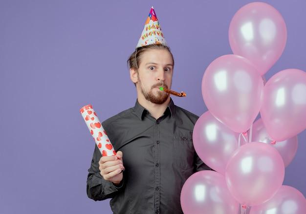 Überraschte gutaussehender mann in der geburtstagskappe hält heliumballons und konfettikanone, die pfeife lokalisiert auf lila wand bläst