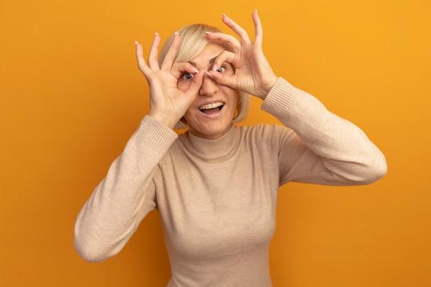 Überraschte hübsche blonde slawische frau, die kamera durch finger auf orange betrachtet