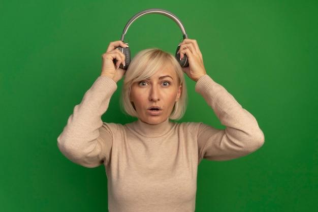 Überraschte hübsche blonde slawische frau hält kopfhörer über kopf auf grün