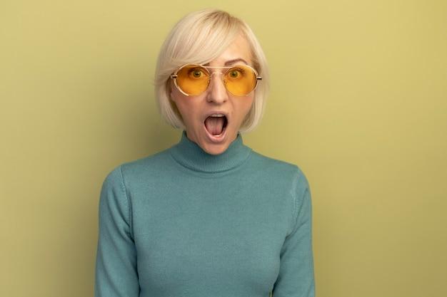 Überraschte hübsche blonde slawische frau in der sonnenbrille betrachtet kamera auf olivgrün