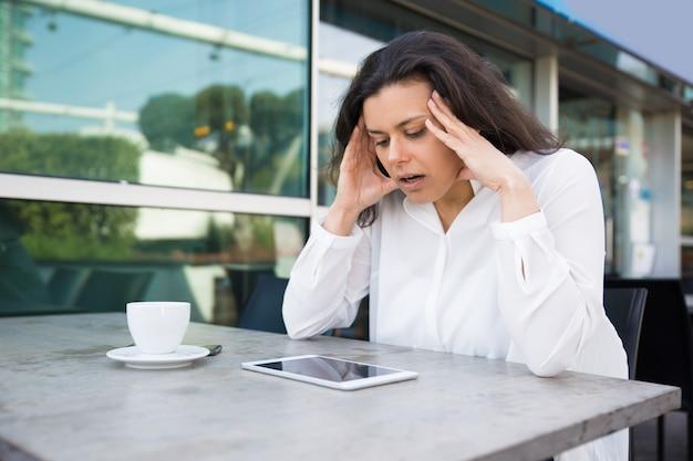 Überraschte hübsche damenlesennachrichten auf tablette im straßencafé