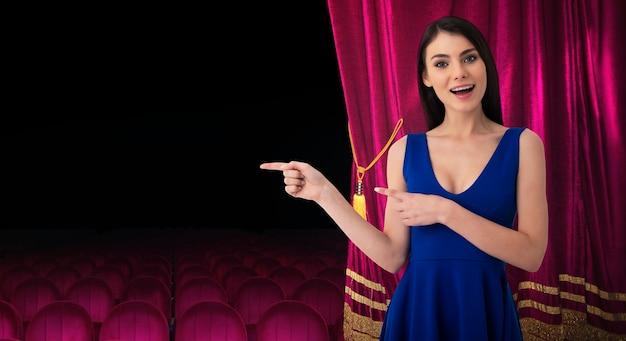 Überraschte hübsche frau vor roten vorhängen deutet auf etwas über die theatershow hin