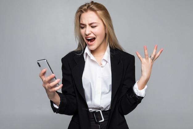 Überraschte hübsche geschäftsfrau, die per telefon steht und isoliert steht.