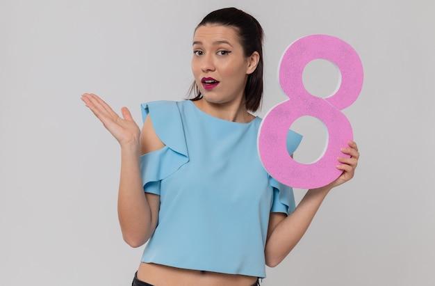 Überraschte hübsche junge frau, die rosa nummer acht hält und ihre hand offen hält