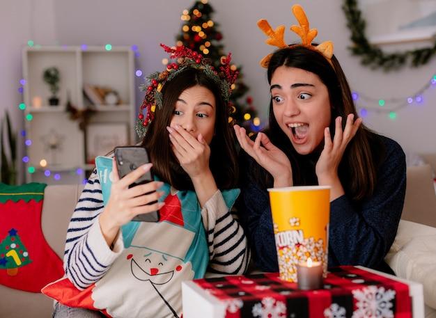 Überraschte hübsche junge mädchen mit stechpalmenkranz und rentierstirnband betrachten telefon, das auf sesseln sitzt und weihnachtszeit zu hause genießt