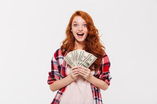 Überraschte hübsche junge rothaarige dame, die geld hält.